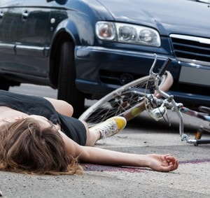Unconscious female cyclist lying on street after road accident